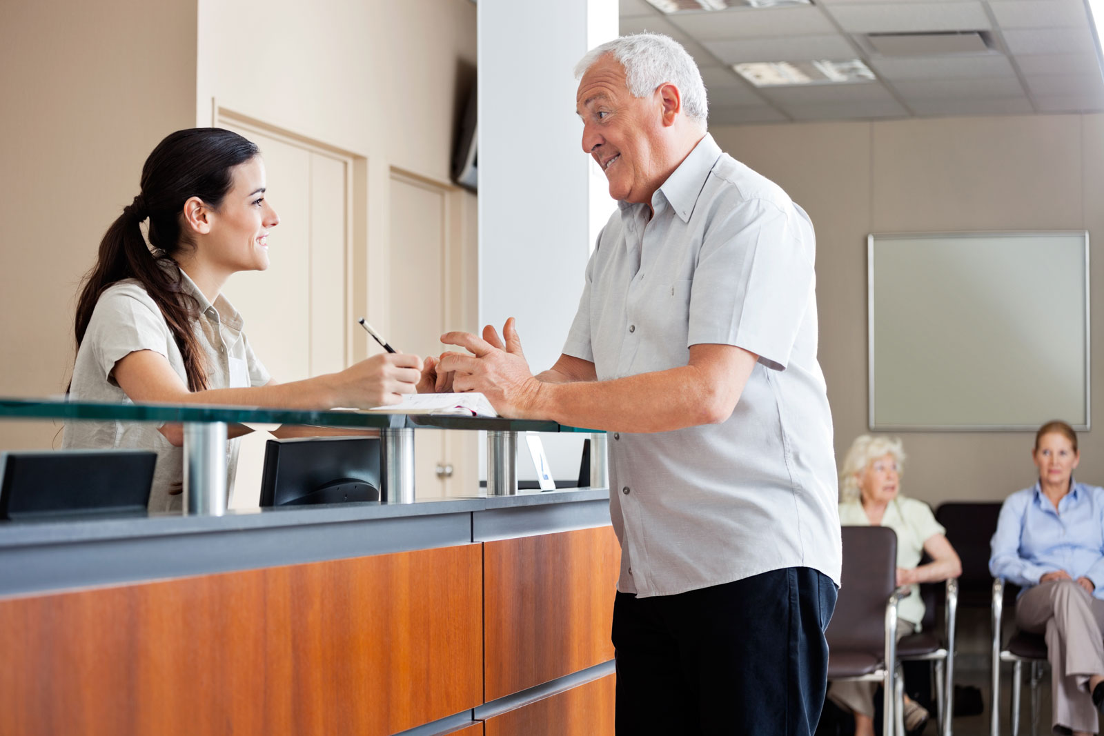 receptionist talking with older patient